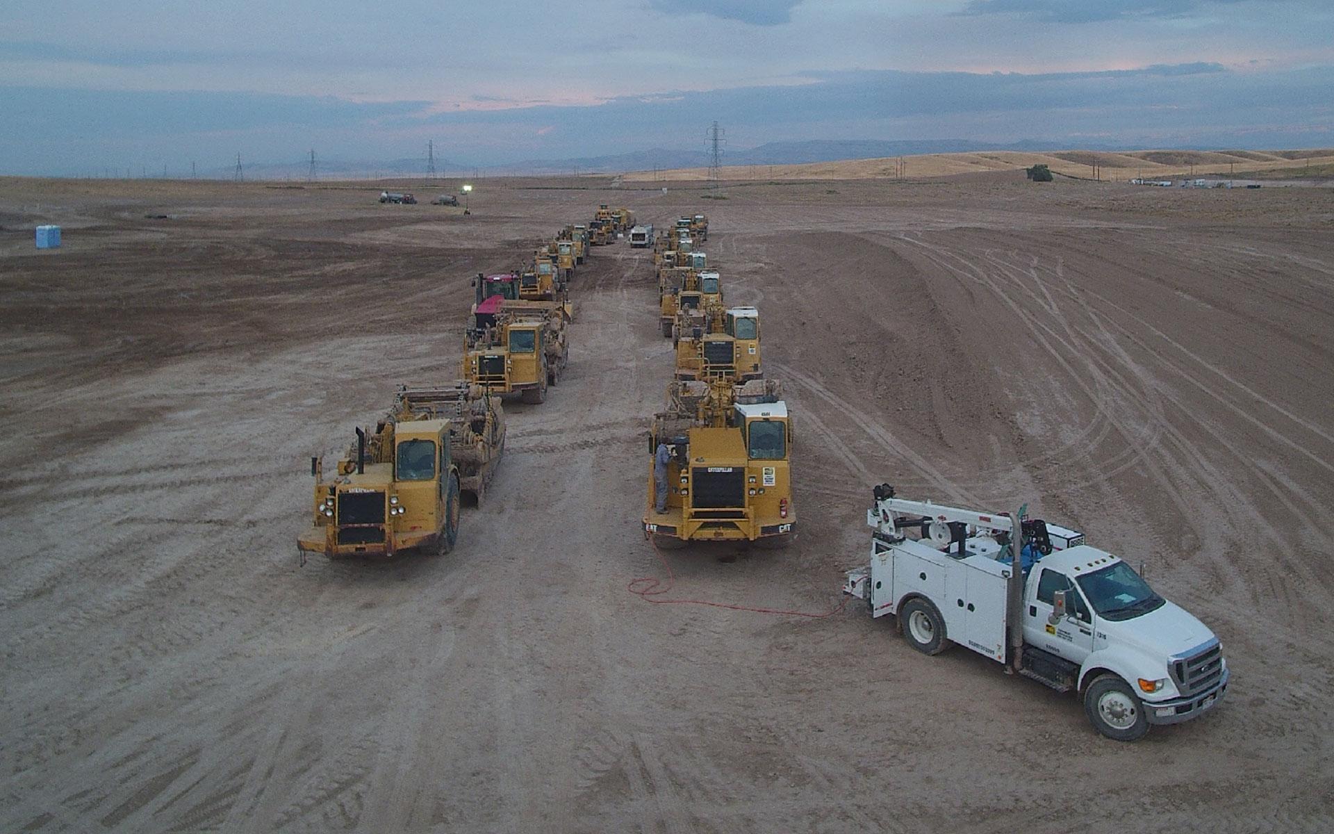 Fleet of tractors on dirt job site